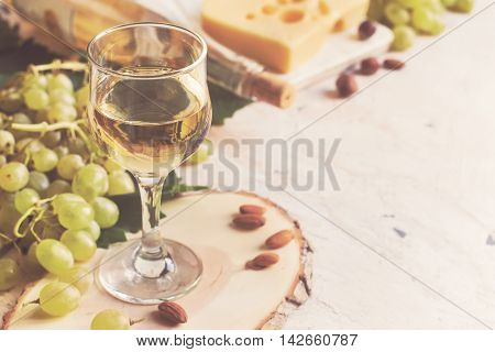 White wine in the glass on the background of grape and cheese tinted copy space