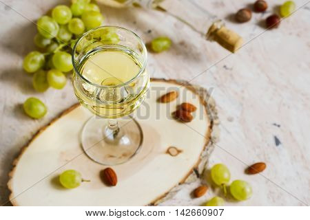 Glass of white wine and a bunch of grapes.