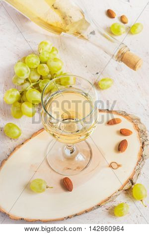 White wine in a glass and a bunch of grapes tinted.