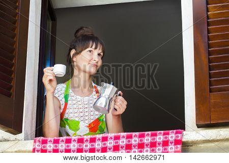 Portrait of happy woman is enjoying hot coffee drink freshly brewed in Italian moka pot sitting near open window with traditional European wood brown shutters