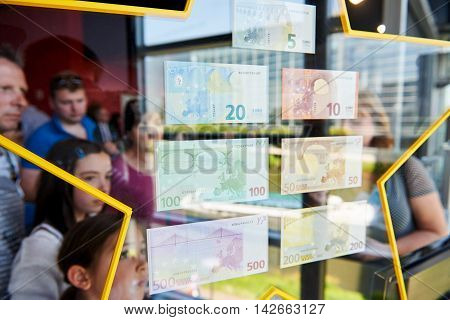 STRASBOURG FRANCE - MAY 8 2016: People admiring all European Union Euro notes with a beautiful reflection of the window and European Parliament in the stars holding them