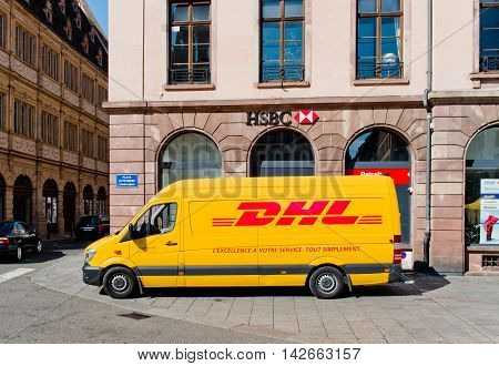 STRASBOURG CIRCA 2016: DHL delivery van leaving after distributing parcels with HSBC bank branch behind in the center of the city