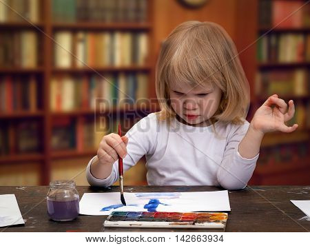 The child draws in the library at the table. Girl little blonde. Multicolored paint brush with blue.