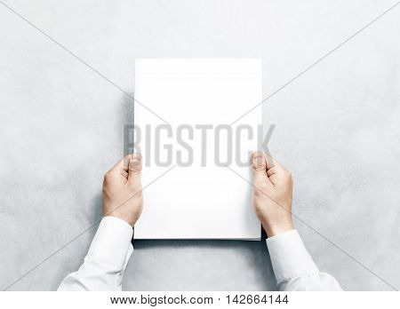 Hand holding white journal with blank cover mockup. Arm in shirt hold clear magazine template mock up. A4 book softcover surface design. Paperback print display show. Closed notebook cover showing.