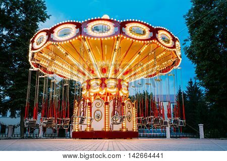 The Brightly Illuminated  Empty Carousel Merry-Go-Round With Seats Suspended On Chains Without People Waiting For Its Visitors. Summer Evening In City Amusement Park.