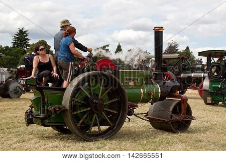 POTTEN END, UK - JULY 27: A vintage steam powered road roller parks up in the main arena having participated in the Grand Parade of steam traction at the Dacorum Steam fair on July 27, 2014 in Potten End