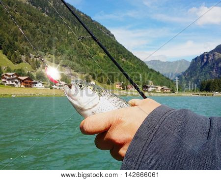 a fisherman holding a rainbow Trout fish