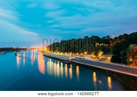 The Scenic Summer Evening View Of Sozh River, Illuminated Embankment And Ancient Greenwood Park, Cathedral Of St. Peter And Paul In Gomel, Homiel, Belarus. Blue Sky Background.