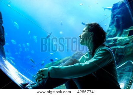 Young Pretty Woman Watching Fishes In A Tropical Aquarium
