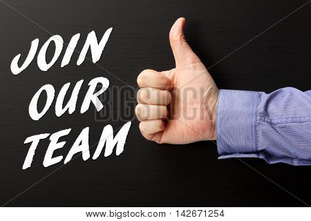 Hand in a business shirt giving the thumbs up sign to the words Join Our Team written on a blackboard in white text