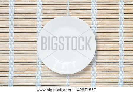 Closeup white ceramic dish on wood mat textured background on dining table in top view