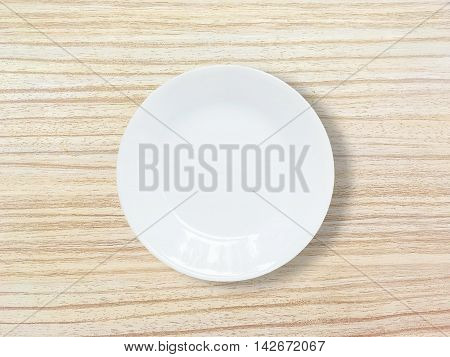 Closeup white ceramic dish on wood dining table textured background in top view
