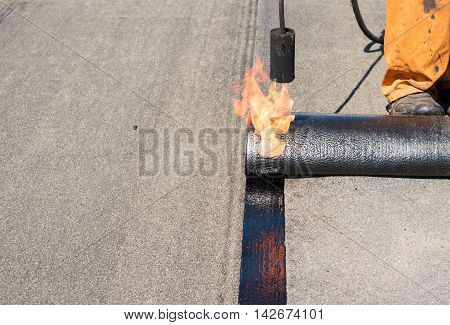 Professional installation of waterproofing on the concrete foundation. Roofer installing Roofing felt with heating and melting of bitumen roll by torch on flame during roof repair
