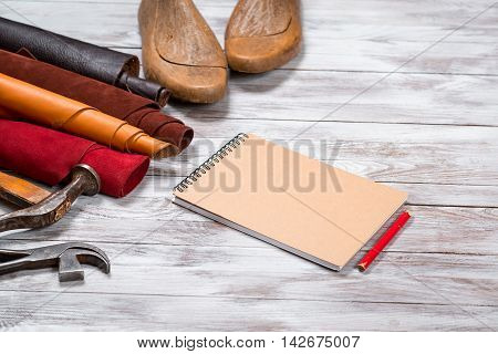 Brightly colored leather in rolls working tools shoe lasts notebook with pencil on white wooden background. Leather craft.