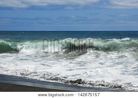 marine landscape Vila Franca atlantic ocean beach in Sao Miguel Azores island of Portugal in summer with vibrant blue sea big wild waves and sand shore foam in travel destination and tourism concept