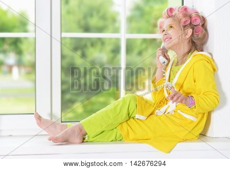 Happy cute little girl in hair curlers and phone