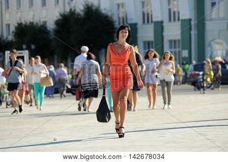 Orel Russia - August 05 2016: Orel city day. Slender woman in red dress walking on the street