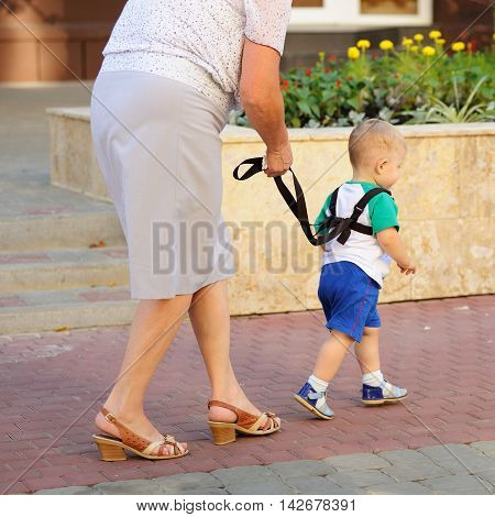 Orel Russia - August 05 2016: Orel city day. Woman walking with toddler on leash closeup
