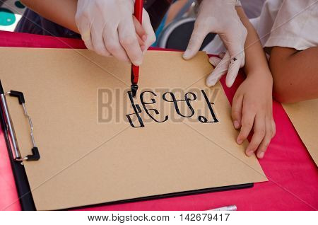 Child writes his name on an old Bulgarian Glagolitic alphabet