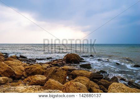 Stormy sea waves on the rocky shore.