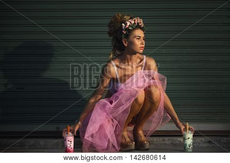Girl with milk against urban wall background.