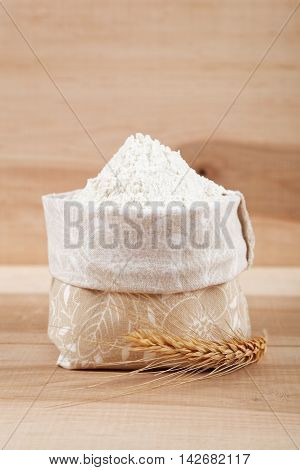 Flour in a canvas bag and ear of wheat on the wooden table.