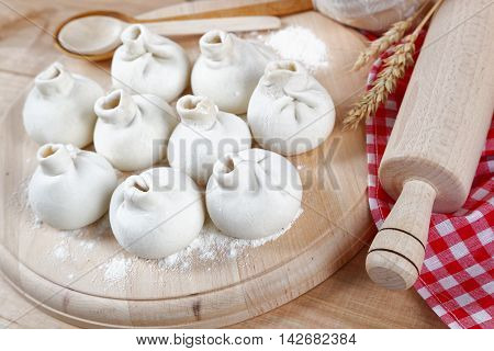 Baking ingredients for cooking manti dumplings on a wooden board.