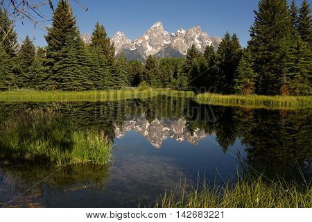 The water is perfectly smooth showing high peak reflections in the Teton's