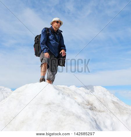 Happy hiker on the top of snowy peak. Active people enjoying outdoor sports in mountain landscape. Healthy lifestyle concept.