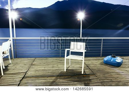white chair on wooden bridge in the sea between kosovo and Albania with led lights