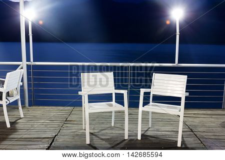 white chairs on wooden bridge in the sea between kosovo and Albania with led lights