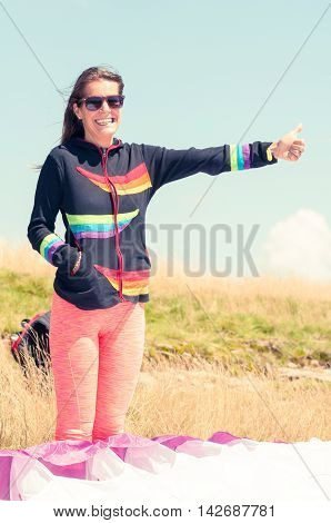 Happy Girl Making Hitchhiking Gesture For Paragliding