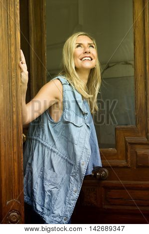 blond woman standing in doorway and looking up into the sky