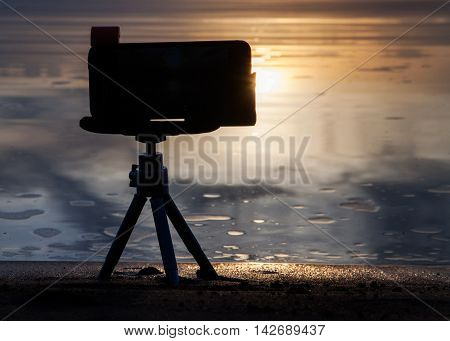 Photo camera on a tripod removes the sunset