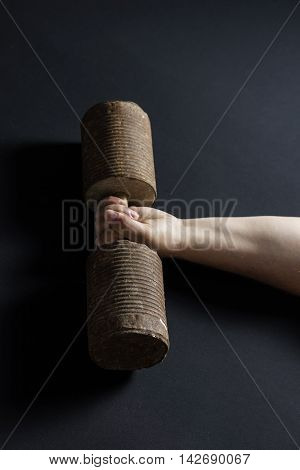 strong hand lifting up a rusty dumbbell