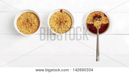 Three crumbles with raspberries gooseberries blackberries and cinnamon. English dessert in a white ceramic mold for baking on white wooden table. Top view. Copyspace.