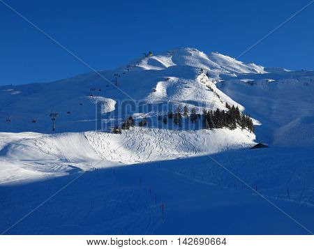 Chair lift going to the top of Mt Klingenstock. Ski slopes and tracks. Winter scene in Stoos Switzerland.