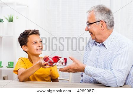 Grandson is giving present to his grandfather.