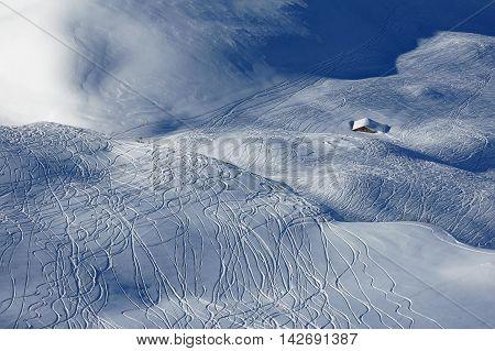 Winter scene in Stoos Swiss Alps. Ski area. Ski and snowboard tracks in powder snow.