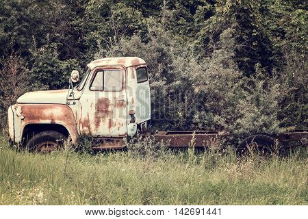 Abandoned old truck rusting in a field