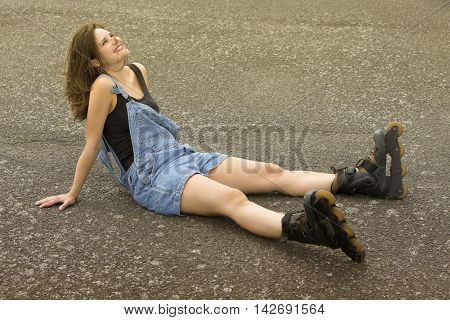 young brunette woman sitting with rollerblades on the street and smiles