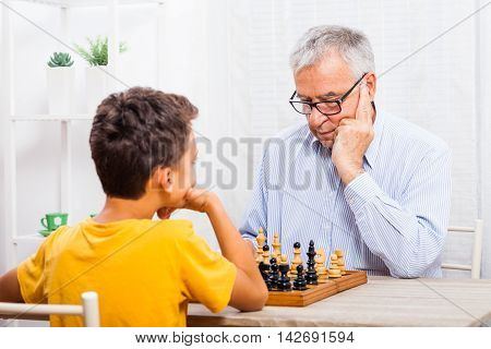 Grandfather and grandson are playing chess at home.
