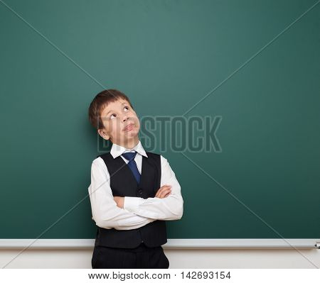 school student boy look up at the clean blackboard, grimacing and emotions, dressed in a black suit, education concept, studio photo