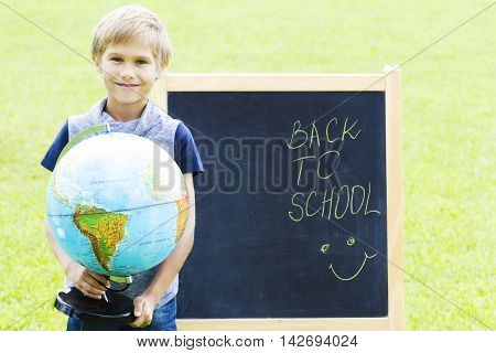 Boy with a globe against the blackboard. Education, Back to school concept