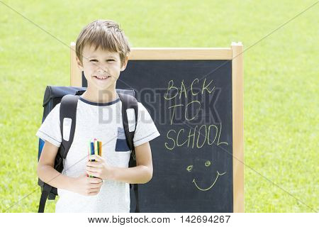 Little boy with pens and backpack against the blackboard. Education, Back to school concept