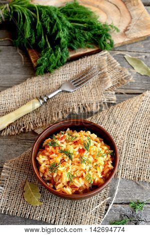 Risotto with vegetables in a clay bowl, fork, dill sprigs, cutting board on old wooden background. Rice cooked with tomatoes, carrots, garlic and spices. Simple and healthy vegetarian rice dish
