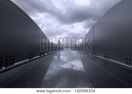 Black and white architecture in rounded shape with dramatic cloudy sky and reflection. Modern geometric architecture photo with dominant blue tones.