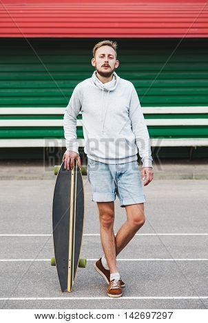 Hipster cool boy standing with the longboard in his hands
