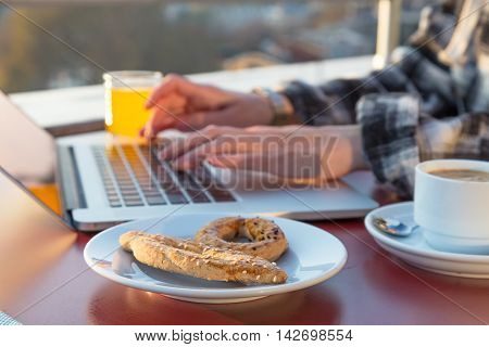 Freelance work Casual dressed woman Person at wooden desk of open Terrace Cafe roof Top working on computer tasty Bakery Coffee and orange Juice