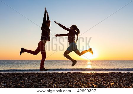 Long awaited Meeting of Friends Man and Woman jumping towards Embrace arms up and opened at pebble Ocean Beach bright Sunrise and blue Sky